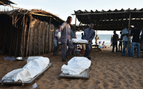 FILE. People carry the body of a victim following after gunmen went on a shooting rampage in the Ivory Coast resort of Grand-Bassam, on 13 March, 2016. Picture: AFP.