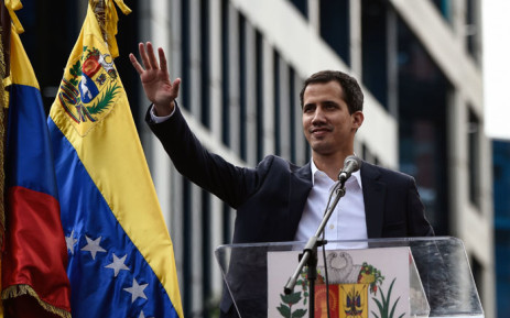 """Venezuela's National Assembly head Juan Guaido waves to the crowd during a mass opposition rally against leader Nicolas Maduro in which he declared himself the country's """"acting president"""", on the anniversary of a 1958 uprising that overthrew military dictatorship, in Caracas on 23 January 2019. Picture: AFP"""