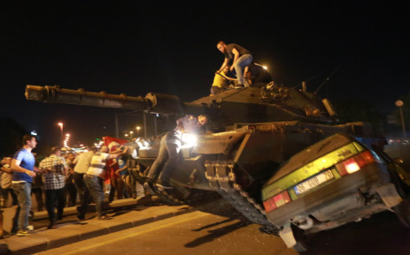 A tank crashes against a car as people take to the streets in Ankara, Turkey, during a protest against a military coup. Picture: AFP.