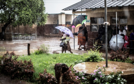 Zambian voters walk under heavy rain to join the queues at a Polling station in Lusaka, Zambia on 20 January, 2015. Picture: AFP.