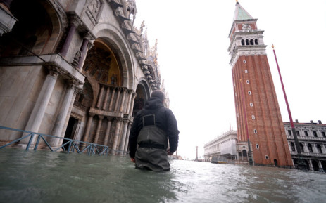"""A man walks in flooded St. Mark square in Venice, during """"acqua alta"""", or high water, of 160 centimetres on 17 November 2019. Picture: AFP"""