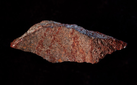 A handout photo released on 12 September 2018 by Nature Publishing Group shows the Blombos Cave drawing with ochre pencil on silcrete stone. The earliest known drawing in history - a red, cross-hatched pattern - has been unearthed in South Africa. Picture: AFP.