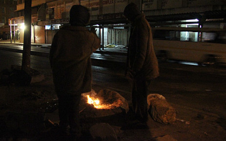 Homeless men keep themselves warm by burning newspapers. Picture: EWN