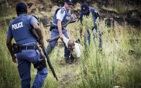 SAPS arrest a very drunk protester after skirmishes along the train line in Krugersdorp. Picture: Thomas Holder/EWN.