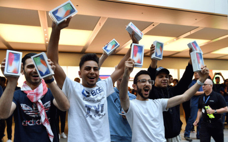 First customers display their iPhone X sets at an Apple showroom in Sydney on 3 November, 2017. Apple iPhone X went for sale in Australia with long queues outside the Apple stores. Picture: AFP.