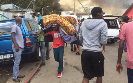 Mandela Park residents salvage their belongings in case the fire spread towards their home. Picture: Monique Mortlock/EWN.