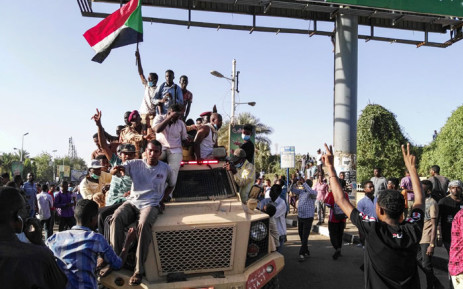 Sudanese protesters wave a national flag and flash the victory sign as they sit atop a military vehicle next to soldiers near the capital Khartoum's military headquarters on 7 April 2019. Picture: AFP