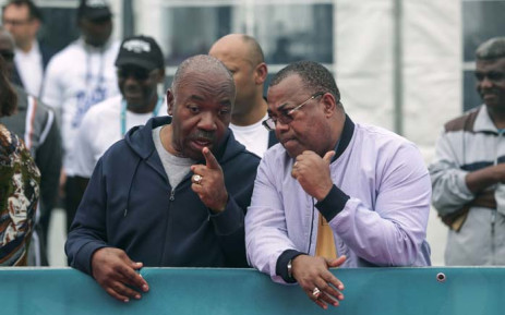 Gabon's President Ali Bongo Ondimba (L) and Gabon's Prime Minister Julien Nkoghe Bekale speak as they attend the Gabon Marathon in Libreville on 30 November 2019. Picture: AFP.