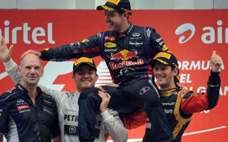 INDIA, NEW DELHI : Red Bull driver Sebastian Vettel (C) of Germany hoisted by Mercedes driver Nico Rosberg (2L) of Germany and Lotus driver Romain Grosjean (R) of France pats Red Bull Chief Technical Officer Adrian Newey (L) after winning the Formula One Indian Grand Prix 2013 at the Buddh International circuit in Greater Noida, on the outskirts of New Delhi on October 27, 2013. AFP PHOTO/Indranil MUKHERJEE