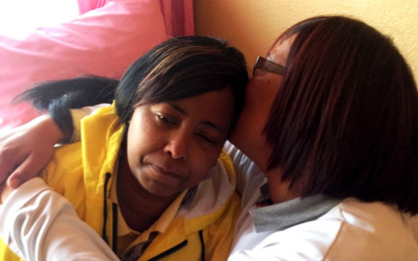 Debra Boards, the aunt of four-year-old Taegrin Morris, who died after being dragged behind a hijacked car on 19 July 2014, is comforted by a friend. Picture: EWN.