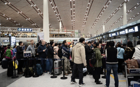 FILE: This file photo shows passengers wait for their flights at the Beijing Capital International airport after heavy snowstorm cancelled and delayed numerous flights in Beijing on 23 November 2015. Picture: AFP.