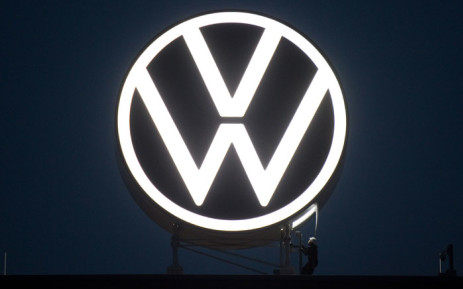 This picture taken on 9 September 2019 shows workers unveiling an illuminated logo of German carmaker Volkswagen (VW) at the company's headquarters in Wolfsburg, northern Germany. Picture: AFP