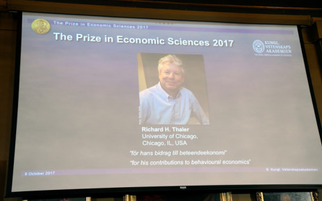 A picture taken on 9 October 2017 in Oslo shows a giant screen bearing a portrait of US economist Richard Thaler after the Norwegian Nobel Committee announced that he won the Nobel economics prize. Picture: AFP