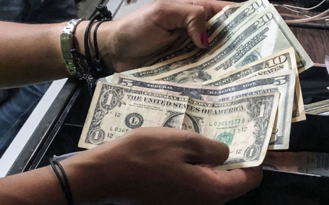 A cashier counts dollar bills at a restaurant. Picture: AFP