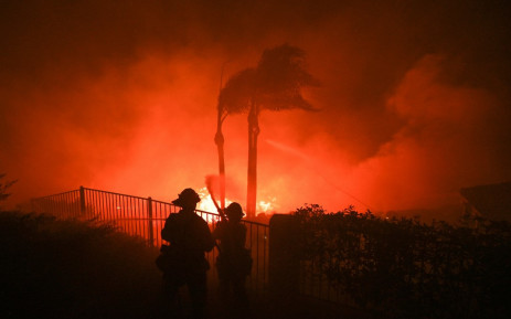 Firefighters try to surpress flames from a home patio at the Blue Ridge Fire in Yorba Linda, California, October 26, 2020. Pic: AFP.