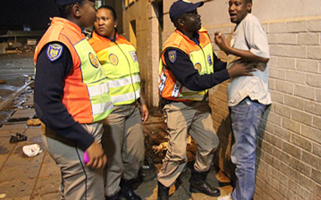 JMPD officers search a man during a patrol in Hillbrow, Johannesburg, on New Year's Eve. Pic: Taurai Maduna/EWN