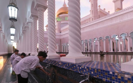 In this picture taken on 1 April 2019 children perform ablution before praying at the Sultan Omar Ali Saifuddien mosque in Bandar Seri Begawan in Brunei. Picture: AFP.