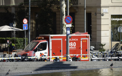 A policeman stands next to an ambulance after a van ploughed into the crowd, injuring several persons on the Rambla in Barcelona on August 17, 2017. Picture: AFP