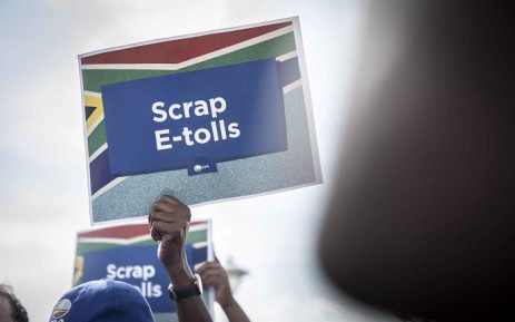Members of the DA holding up placards as DA Gauteng Premier candidate Solly Msimanga burns e-toll statements outside the Sanral offices in Centurion on 4 April 2019. Picture: Abigail Javier/EWN