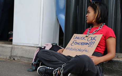 A Wits University student sits on the ground during a third day of protests on campus over proposed tuition fee increases on 16 October 2015. Picture: Reinart Toerien/EWN