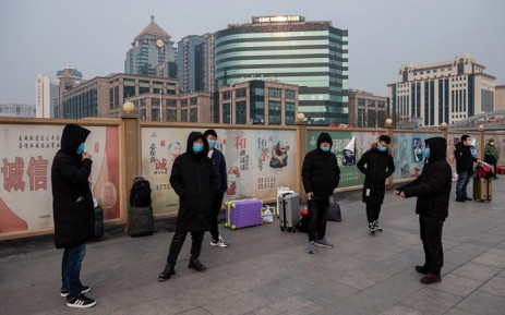 People wearing protective masks to help stop the spread of a deadly virus which began in Wuhan, wait next to their suitcases at the Beijing railway station in Beijing on 27 January 2020. Picture: AFP