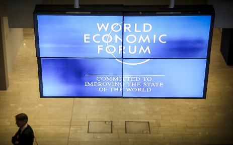 A delegate at the World Economic Forum 2015 stand underneath one of the forum's monitors. Picture: Thomas Holder/EWN
