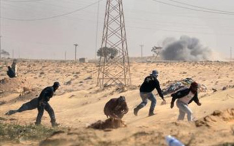 Libyan rebels run to cover as a tank shell of government forces explodes nearby on March 24, 2011. Picture: AFP