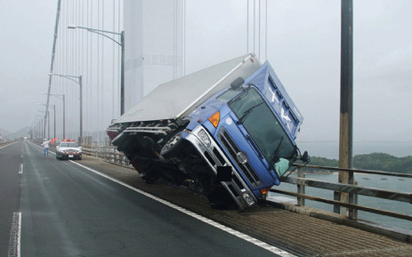 This handout photo released by the Kagawa Prefectural Police on 4 September 2018 and received via Jiji Press shows a truck sitting at an angle after being blown over by strong winds caused by Typhoon Jebi on the Seto Ohashi bridge in Sakade, Kagawa prefecture on Japan's Shikoku island. Picture: AFP