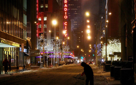 A man shovels on 50th street looking towards Radio City Music Hall in New York as the entire Northeast United States braces itself for a major snow storm on 26 January 2015.