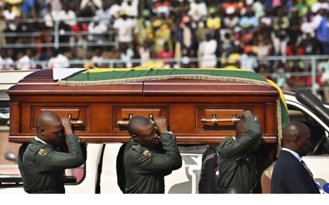 The casket containing the body of Zimbabwe's late former President Robert Mugabe is hoisted by soldiers in ceremonial uniform after it arrived on 12 September 2019 at the historic Rufaro Stadium in the capital, Harare, where his body will lie in state for members of the public file past. Picture: AFP