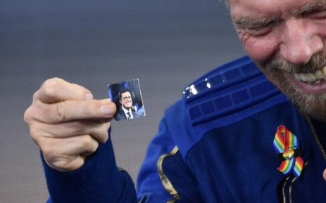 """Sir Richard Branson holds up a photo of comedian Stephen Colbert that he brought with him into space, as he speaks after flying into space aboard a Virgin Galactic vessel, a voyage he described as the """"experience of a lifetime"""". Picture: AFP."""