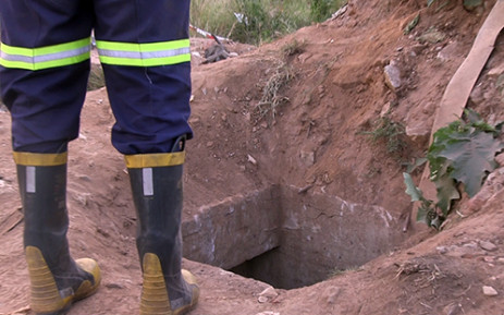 A rescue worker stands next to the illegal mine shaft where eleven miners were rescued after being trapped underground for almost a day on 16 February 2014. Picture: Reinart Toerien/EWN