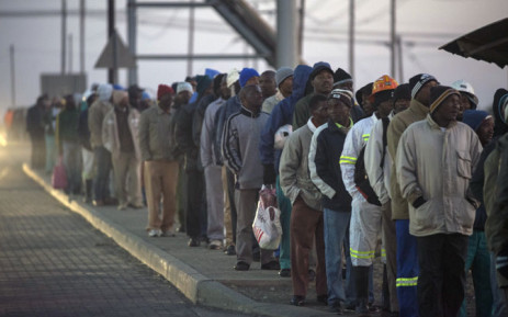 FILE: South African platinum miners queue to undergo essential medical and safety procedures before working, early on 25 June 2014 at the Wonderkop mines in Marikana Rustenburg, after a five month long strike. Picture: AFP.