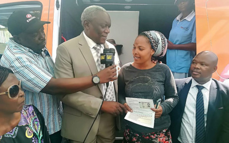 Home Affairs Minister Siybonga Cwele on 14 December 2018 hands out ID books and birth certificates to Alexandra residents affected by last week's fire. Picture: @HomeAffairsSA/Twitter