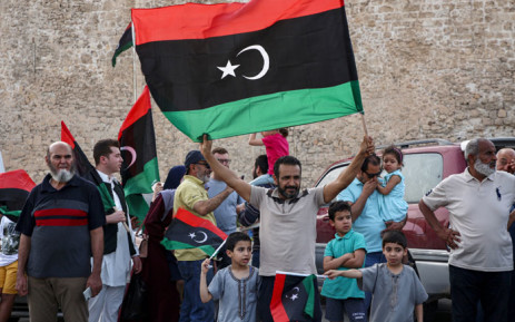 A man waves a Libyan national flag as people celebrate in the capital Tripoli on 4 June 2020, after the UN-recognised Government of National Accord (GNA) said it was back in full control of the capital and its suburbs. The announcement came after GNA forces retook the Tripoli International Airport on 3 June after fierce battles more than a year after losing it as Haftar launched an offensive to seize the capital. Picture: AFP