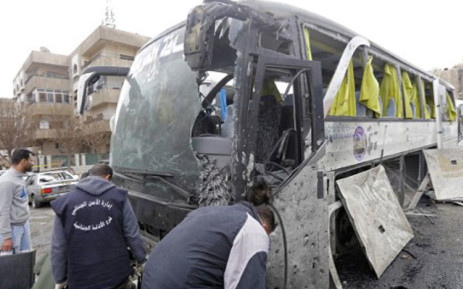 Syrian forensics examine a damaged bus at the scene of a bombing following twin attacks targeting Shiite pilgrims in Damascus' Old City on March 11, 2017. Picture: AFP.