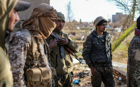 Fighters with the Syrian Democratic Forces (SDF) check a makeshift camp for Islamic State (IS) group members and their families in the town of Baghouz, in the eastern Syrian province of Deir Ezzor, on 9 March 2019. Picture: AFP