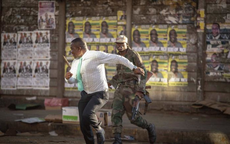 A man runs from an army officer during post-election protests in Zimbabwe on 1 August 2018. Picture: Thomas Holder/EWN