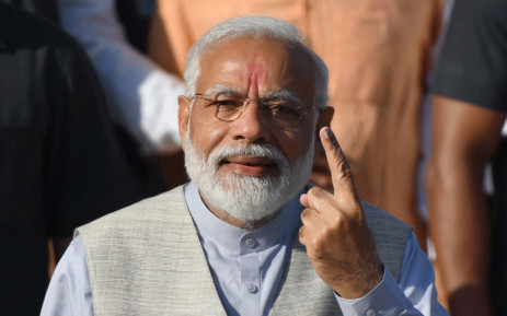 FILE: Indian Prime Minister Narendra Modi displays his ink-marked finger after casting his vote during the third phase of general elections at a polling station in Ahmedabad on 23 April 2019. Picture: AFP