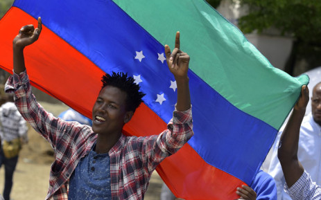 A young man reacts in front of the unofficial green, blue and red flag of the advocated region for the Sidama ethnic group as people of the Sidama ethnic group, the largest in southern Ethiopia, celebrate at Hawassa city over plans by local elders to declare the establishment of a breakaway region for the Sidama later this week, in Awasa, 15 July 2019. Picture: AFP
