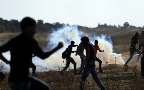 FILE: Palestinian protesters run for cover from teargas shot by Israeli soldiers during clashes near the border fence between Israel and the central Gaza Strip east of Bureij on 16 October 2015. Picture: AFP