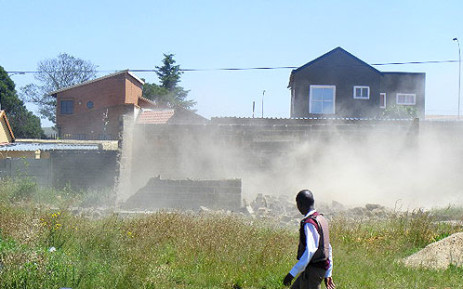 A man walks past a house in Lenasia which was demolished on 19 November 2012. Picture: iWitness