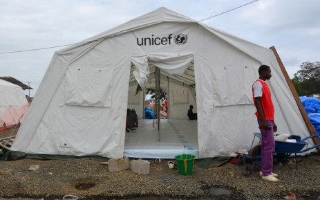 FILE: A man stands next to a tent set up to treat Ebola patients. Picture: AFP