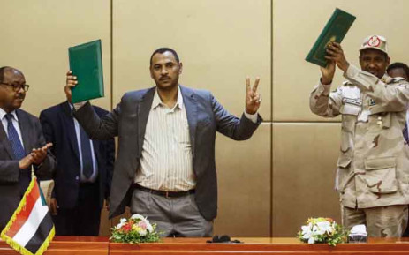 (L to R) Ethiopian mediator Mahmoud Drir, protest leader Ahmad Rabie, and General Mohamed Hamdan Daglo, Sudan's deputy head of the Transitional Military Council, celebrate after signing the constitutional declaration, at a ceremony attended by African Union and Ethiopian mediators in the capital Khartoum on 4 August 2019. Picture: AFP