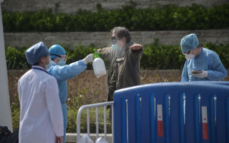 A man who has recovered from the COVID-19 coronavirus infection is disinfected by medical staff before he leaves the makeshift Wuchan hospital in Wuhan in China's central Hubei province on 10 March 2020. Picture: AFP