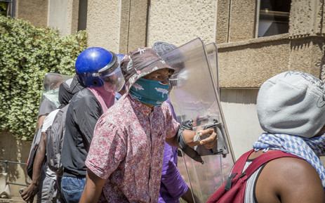 FILE: Masked #FeesMustFall supporters carry police shields and rocks during protests over tertiary education fees at Wits University's main campus on 11 October 2016. Picture: Reinart Toerien/EWN.