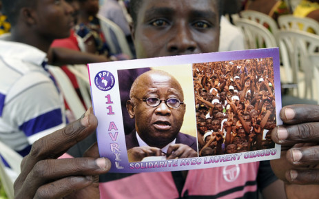 "A supporter of Ivory Coast's former president Laurent Gbagbo holds a flyer picturing Gbagbo and reading in French ""April 11 Solidarity with Laurent Gbagbo"" during a demonstration on April 11, 2015 in Abidjan on the anniversary of Gbagbo's arrest by the International Criminal Court of The Hague, on charges of crimes against humanity after post-election violence in 2011. Picture: AFP."