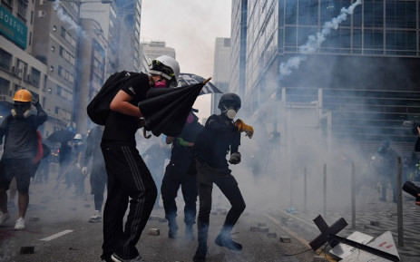 FILE: A protester throws back a tear gas canister during clashes with riot police at Kowloon Bay in Hong Kong on 24 August 2019, in the latest opposition to a planned extradition law that has since morphed into a wider call for democratic rights in the semi-autonomous city. Picture: AFP