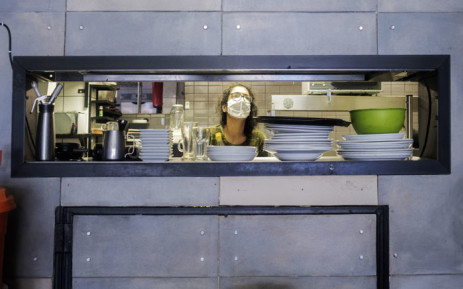 A worker prepares a restaurant to reopen for food deliveries in Melville, Johannesburg, on 1 May 2020, in accordance with the Stage 4 lockdown regulations. Picture: AFP