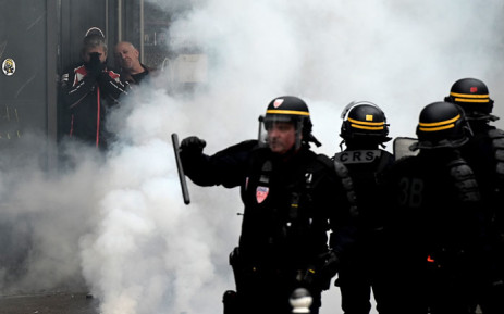 Protesters hide from tear gas smokes as riot police officers walk on place d'Italie in Paris on 16 November 2019. Picture: AFP